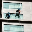 Two men cleaning windows on a high rise building - Stock Photo