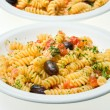 Fusilli with cheese, fresh tomatoes and olives. — Stock Photo #12423444