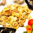 Tasty Orecchiette pasta with mussels, clams and vegetables. - Stock Photo