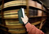 Hand bedrijf boek in bibliotheek — Stockfoto