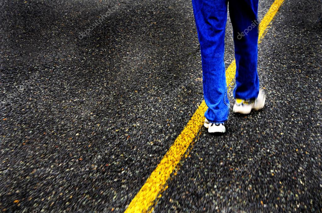 Person wearing blue jeans walking down yellow line of road — Stock Photo #14410263