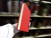 Hand met rode boek in de bibliotheek — Stockfoto