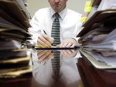 Businessman at Desk with Piles of Files — Stock Photo