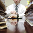 Businessman at Desk with Files Pointing at Watch — Photo
