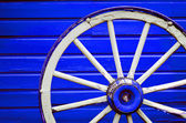 Wagon Wheel by Painted Blue Wall — Stock Photo