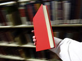 Hand Holding Red Book in Library — Stock Photo