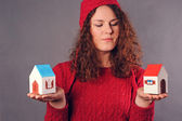 Woman and two houses in hands — Stock Photo