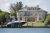 Luxurious waterfront mansion with a boat — Stok fotoğraf