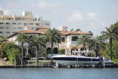 Luxurious waterfront mansion with a boat — Stock Photo