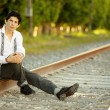 Latino man sitting on railroad tracks — Stock Photo