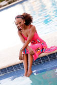 Jamaican woman sitting by the pool — Stock Photo