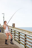 Woman fishing from a pier — Stok fotoğraf