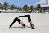 Woman performing yoga on the beach stock image — Stock Photo
