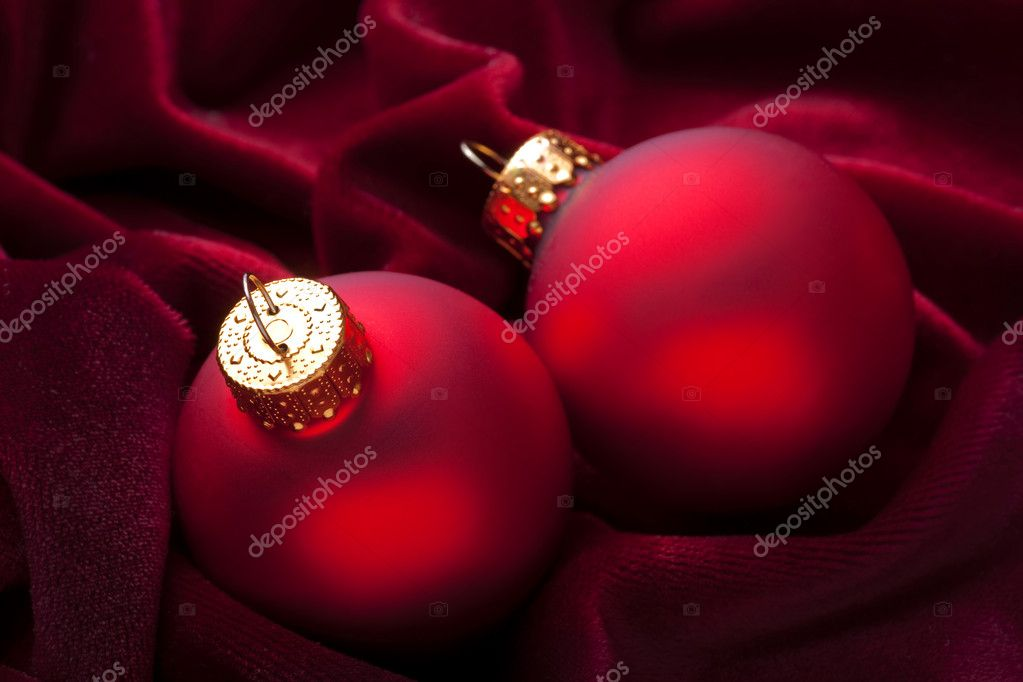 Traditional red Christmas ornaments on rumpled red velvet. — Stock Photo #13428068
