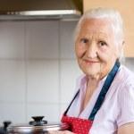 Elderly woman in a kitchen — Stock Photo