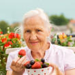 Elderly woman with berries — Stock Photo #12710622