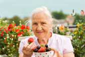 Elderly woman with berries — Stock Photo