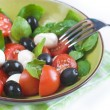 Salad with tomatoes, mozarella, olives and basil - Stock Photo