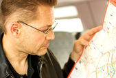 Serious man looking at a map — Stock Photo
