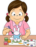 Girl Painting a Rabbit Figurine — Stock Photo