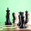 Chess pieces on board. Focus on the black king — Stock Photo #12561518