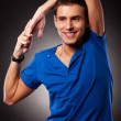 Young casual man stretching his hand above his head — Stock Photo