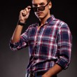Young casual man taking down his sunglasses — Stock Photo #12561431
