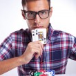 Young casual man with eyeglasses showing his poker hand - Stock Photo