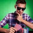 Man looking thoughtfully at his poker hand — Stock Photo