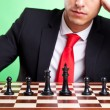 Business man standing in front of chess line-up - Stock Photo