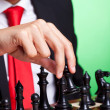Business man playing chess black makes first move — Stock Photo