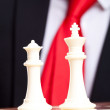 White chess king and queen in front of business suit — Stock Photo #12561533