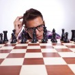 Постер, плакат: Pensive man in front of his first chess move