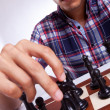 A young casual man moving his chess piece - Stock Photo