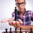 Young man chess player holding up his king — Stock Photo