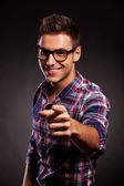 Young casual man with spectacles pointing at the camera — Stock Photo
