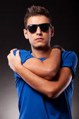 Young casual man with hands crossed on his shoulders — Stock Photo
