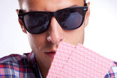 Young gambler with sunglasses holding his poker hand up — Stock Photo