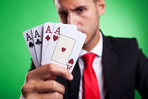 Young business man showing a four of a kind hand of aces — Stock Photo