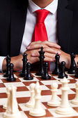 Business man standing in front of unstarted chess game — Stock Photo