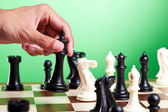 Human hand moves king on chessboard — Stock Photo