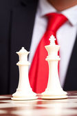 Ajedrez blanco rey y la reina frente a traje de negocios — Foto de Stock