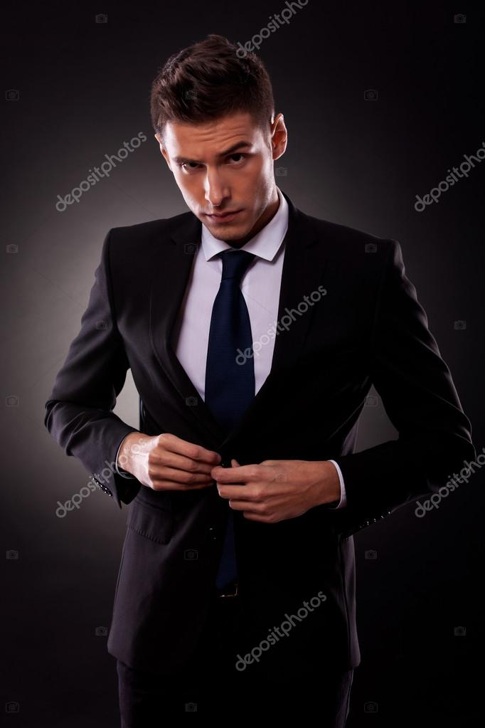 Businessman buttoning jacket, getting dressed, on dark background   Stock Photo #12561417