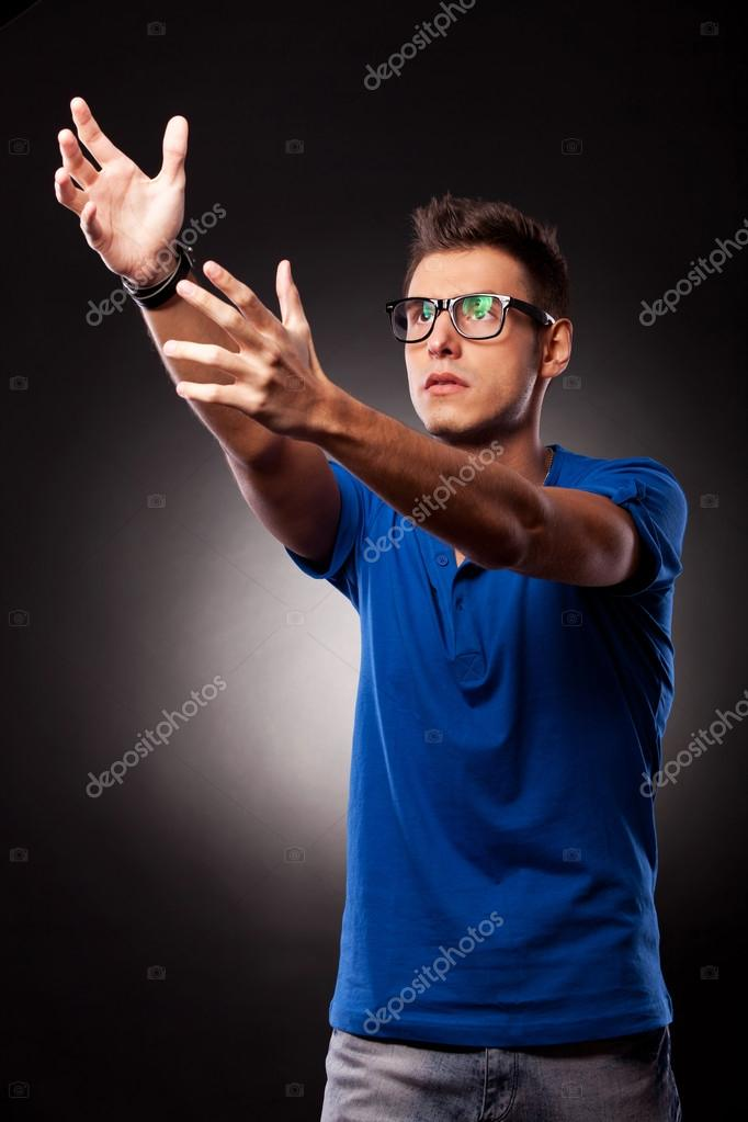 Young casual man holding his hands up, trying to catch or to reach something, over black background — Stock Photo #12561456