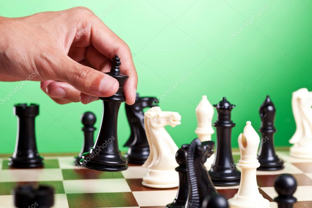 Human hand moves king on chessboard. Green background — Stock Photo #12561517