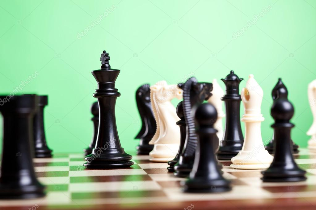 Chess pieces on board. Focus on the black king. Green background. — Stock Photo #12561518