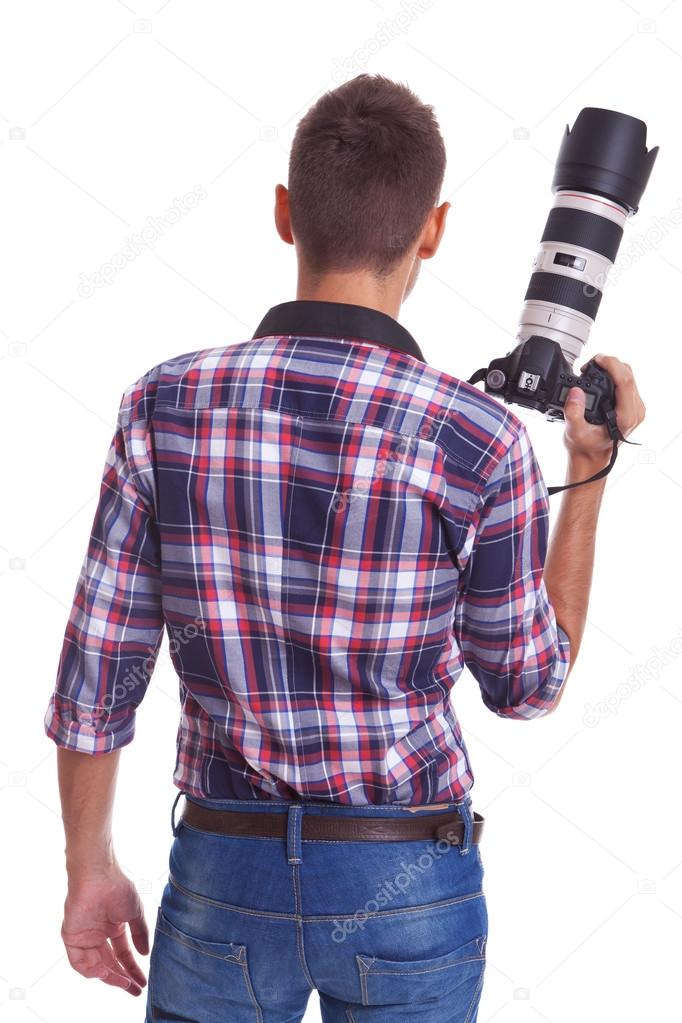 Back view of a professional male photographer holding his big camera . isolated on white background  — Stock Photo #12561551