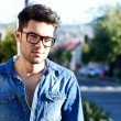 Casual young man smiling in the street - Foto Stock