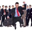 Young leader jumping for joy in front of his team — Stock Photo