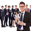 Businss man holding a trophy in fron of his team — Stockfoto